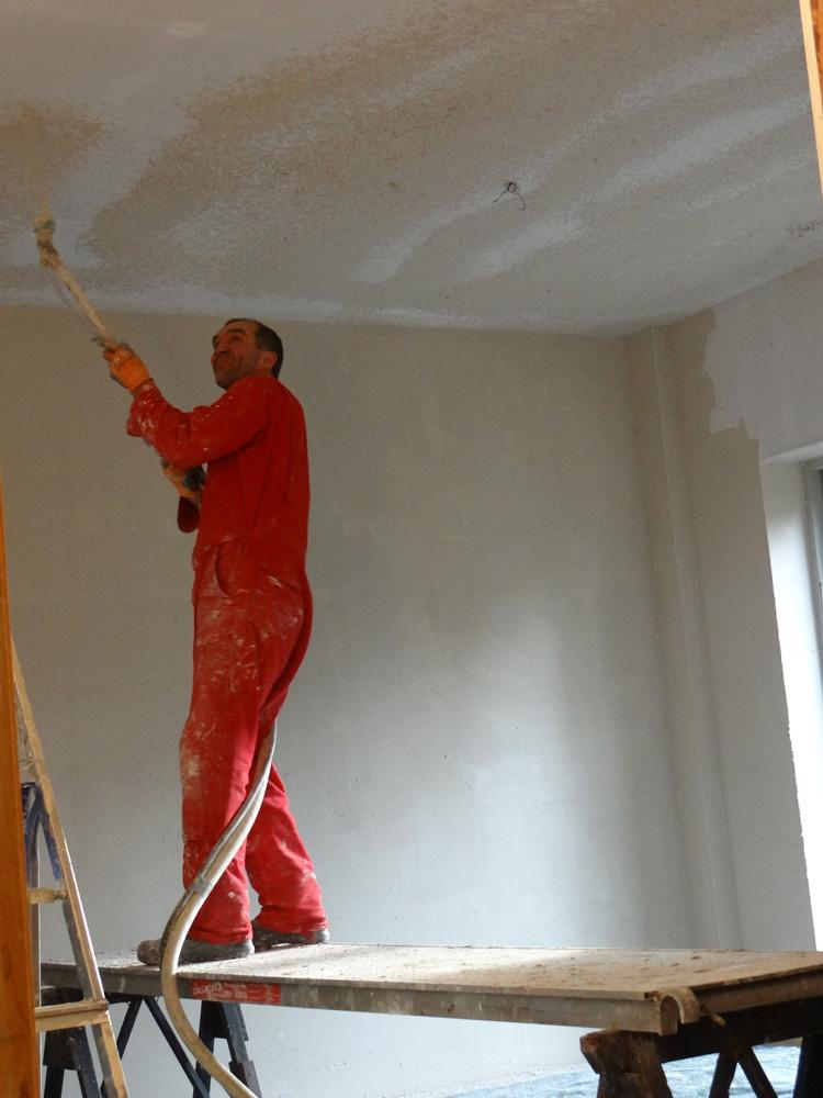 Leempoeder en water worden vermengd in een machine. Via een slag wordt het tegen de muur of het plafond gespoten.