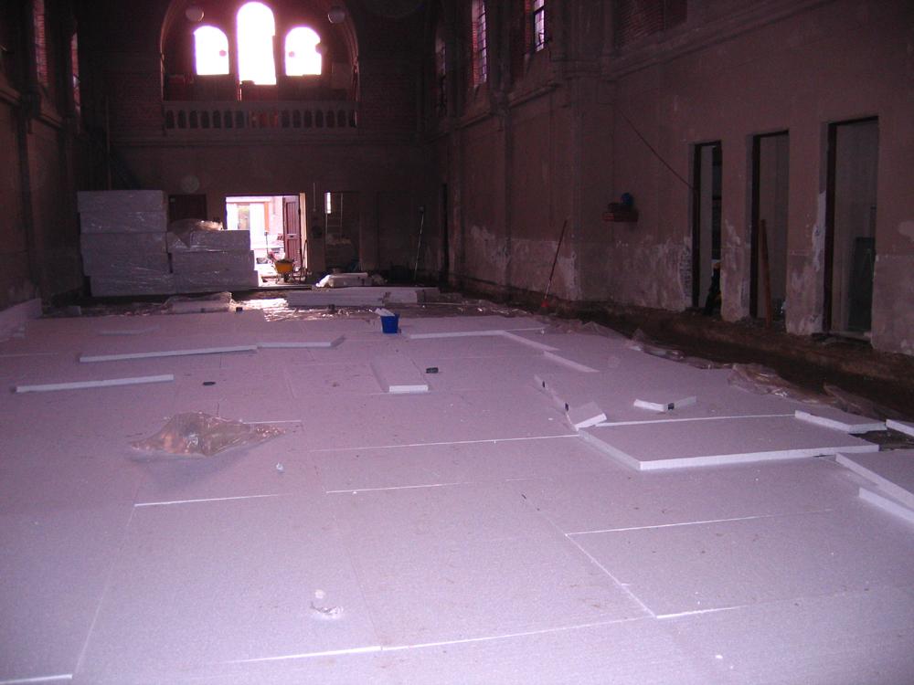 De kerk krijgt een betonnen ondervloer die los komt te liggen van de muren. Hier de voorbereidingen. Het rioolsysteem, ook nieuw aangelegd, ligt onder de isolatie.