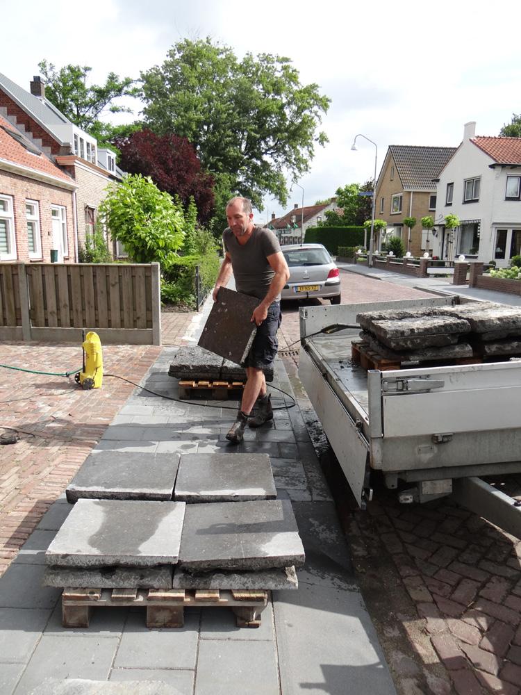 Belgisch hardstenen tegels die eerst buiten voor de kerk lagen, worden nu schoon gespoten om daarna als douchetegel gebruikt te gaan worden.